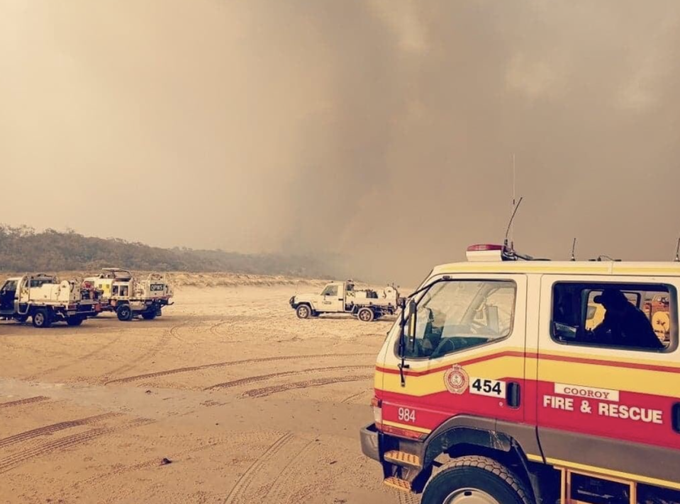 Fire trucks parked on the sand on Fraser Island as smoke looms overhead.