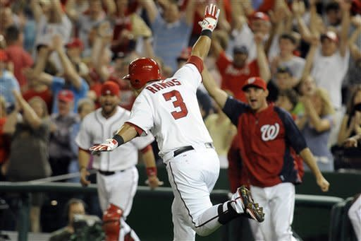 Washington Nationals' Wilson Ramos celebrates his game-winning hit scoring Steve Lombardozzi in the 11th inning to defeat the Philadelphia Phillies 4-3 during their baseball game at Nationals Park, Friday, May 4, 2012, in Washington. (AP Photo/Richard Lipski)