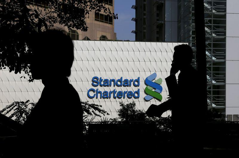 File photo of people walking past the main branch of Standard Chartered in Hong Kong