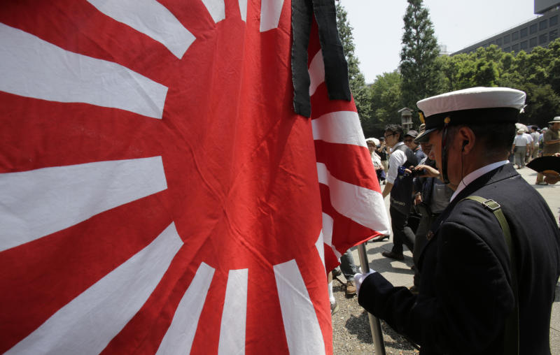 A Japanese clad in a navy costume holds a Japanese military flag as he pays respects to the nation's war dead at the Yasukuni Shrine in Tokyo Thursday, Aug. 15, 2013. Japan marked the 68th anniversary of its surrender in World War II with somber ceremonies Thursday and visits by senior politicians to the shrine honoring 2.5 million war dead that remains a galling reminder of colonial and wartime aggression. (AP Photo/Shizuo Kambayashi)