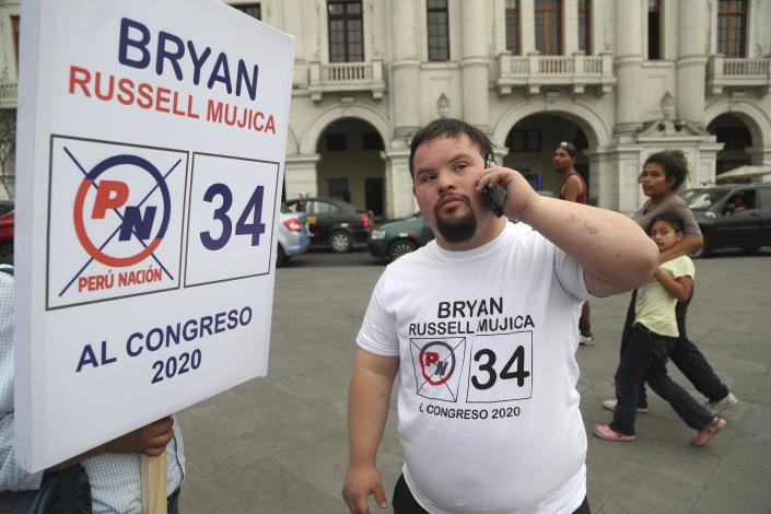 In this Dec. 13, 2019 photo, Bryan Russell takes a call as he campaigns for Congress in Lima, Peru. Russell is the first person with Down syndrome to run for public office, according to the Global Down Syndrome Foundation. (AP Photo/Martin Mejia)