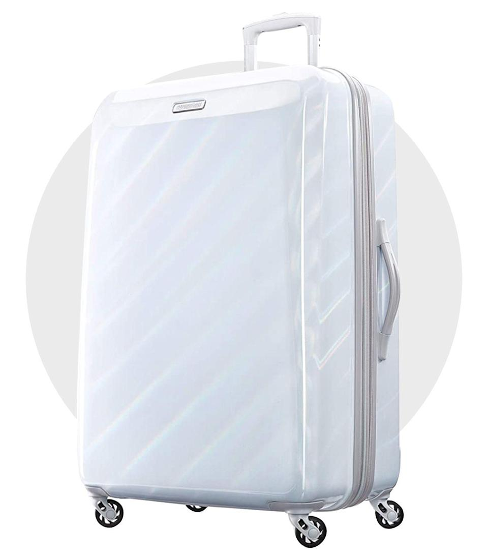 """<p><strong>American Tourister</strong></p><p>amazon.com</p><p><strong>$135.99</strong></p><p><a href=""""https://www.amazon.com/dp/B0849G9TRH?tag=syn-yahoo-20&ascsubtag=%5Bartid%7C1782.g.36450480%5Bsrc%7Cyahoo-us"""" rel=""""nofollow noopener"""" target=""""_blank"""" data-ylk=""""slk:Shop Now"""" class=""""link rapid-noclick-resp"""">Shop Now</a></p><p>Oversized 360-degree spinner wheels that glide over any surface like butter? Say less. The glossy iridescent white color of this suitcase isn't too shabby either, and the light tone is sure to stand out on the conveyer belt in a sea of dark-colored bags. </p>"""