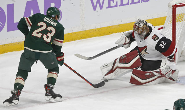 Arizona Coyotes goalie Antti Raanta, right, of Finland, stops a shot by Minnesota Wild's J.T. Brown during the first period of an NHL hockey game Tuesday, Nov. 27, 2018, in St. Paul, Minn. (AP Photo/Jim Mone)