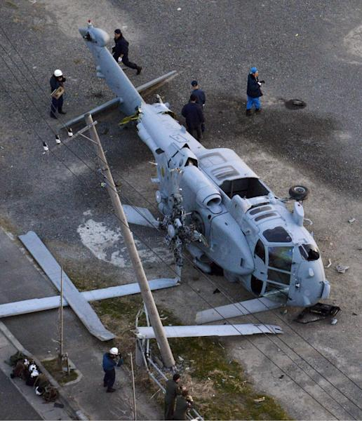 A U.S. Navy MH-60 helicopter lies on the ground after making an emergency landing in Miura city, near Tokyo, Monday, Dec. 16, 2013. U.S. Forces Japan spokesman said two injured crew members from the helicopter were taken to a hospital for treatment. (AP Photo/Kyodo News) JAPAN OUT, MANDATORY CREDIT