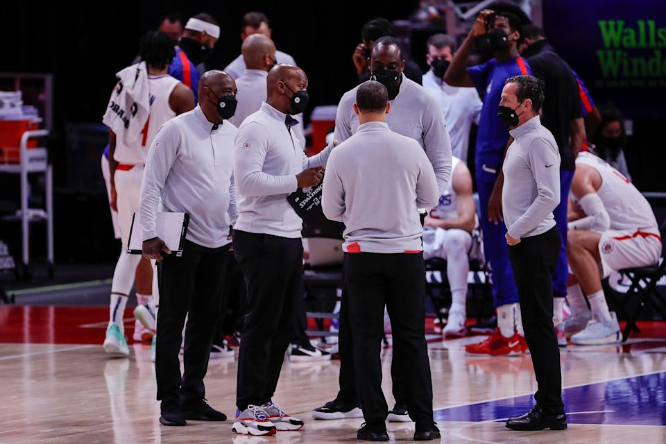L.A. Clippers assistant coach Chauncey Billups, center, talks with the coaching staff during a timeout in the first half against the Detroit Pistons at Little Caesars Arena in Detroit on April 14, 2021.