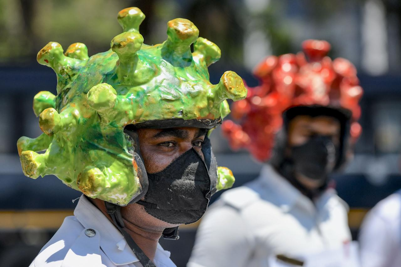 Traffic police personnel wearing coronavirus-themed helmets participate in a campaign to educate the public during a government-imposed nationwide lockdown as a preventive measure against the COVID-19 coronavirus in Bangalore on March 31, 2020. (Photo by Manjunath Kiran / AFP) (Photo by MANJUNATH KIRAN/AFP via Getty Images)
