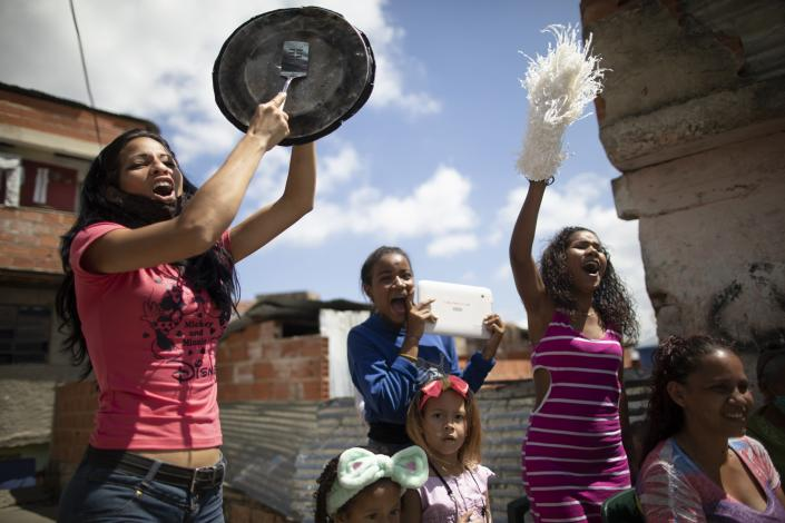 Neighbors cheer during a homespun beauty pageant to pick their child queen for the upcoming carnival festivities in the Antimano neighborhood of Caracas, Venezuela, Friday, Feb. 5, 2021. Neighborhood organizers said they're trying to revive this carnival pageant tradition that's been lost in recent years of economic and political crisis. (AP Photo/Ariana Cubillos)
