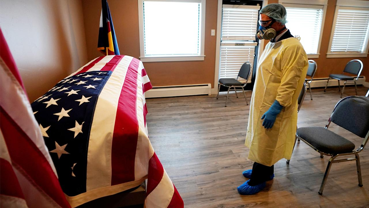 Michael Neel, funeral director of of All Veterans Funeral and Cremation, wearing full PPE, looks at the U.S. flag on the casket of George Trefren, a 90 year old Korean War veteran who died of the coronavirus disease (COVID-19) in a nursing home, in Denver, Colorado, U.S. April 23, 2020. REUTERS/Rick Wilking     TPX IMAGES OF THE DAY