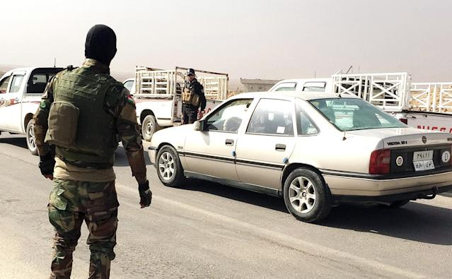 Peshmerga soldier Achmed, left, directs traffic at last checkpoint before Nawaran encampment. His fiancée and friends are in Mosul, and he hopes one day to go to America. (Photo: Ash Gallagher for Yahoo News)