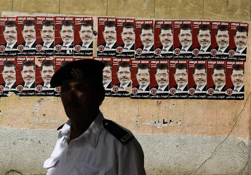 An Egyptian policeman stands by posters of presidential election candidate Mohammed Morsi Thursday, May 24, 2012, outside a polling station in Cairo, Egypt. In a wide-open race that will define the nation's future political course, Egyptians voted Thursday on the second day of a landmark presidential election that will produce a successor to longtime authoritarian ruler Hosni Mubarak. (AP Photo/Hasan Jamali)