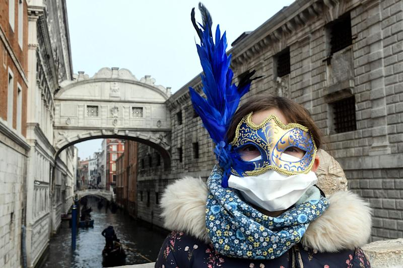 Image: A young tourist wearing a protective facemask and a Carnival mask visits the streets of Venice