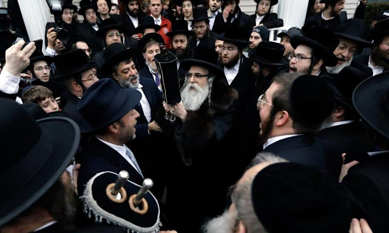 Rabbi Chaim Rottenberg, center, leads Ultra-Orthodox Jews in the inauguration of a Torah scroll ceremony on Sunday outside his home in Monsey.