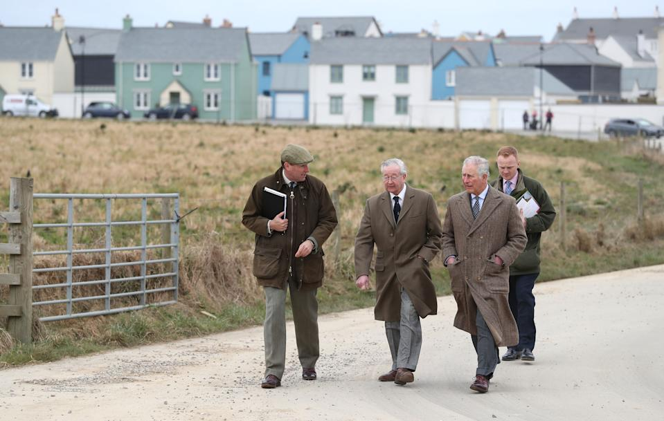 NEWQUAY, ENGLAND - MARCH 22:  Prince Charles, Prince of Wales walks with Alastair Martin, Duchy of Cornwall Secretary & Keeper of the Records (L) and Michael Galsworthy (C) during a visit to Nansledan in Cornwall where he met local residents and unveiled a plaque for the development's new school on March 22, 2018 in Nansledan, England. Nansledan is an extension to the Cornish coastal town of Newquay built on Duchy of Cornwall land and embodies the principles of architecture and urban planning championed by the prince. (Photo by  Andrew Matthews - WPA Pool/Getty Images)