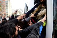 Migrants try to get on a bus which will take them to the Turkish-Greek border, in Istanbul