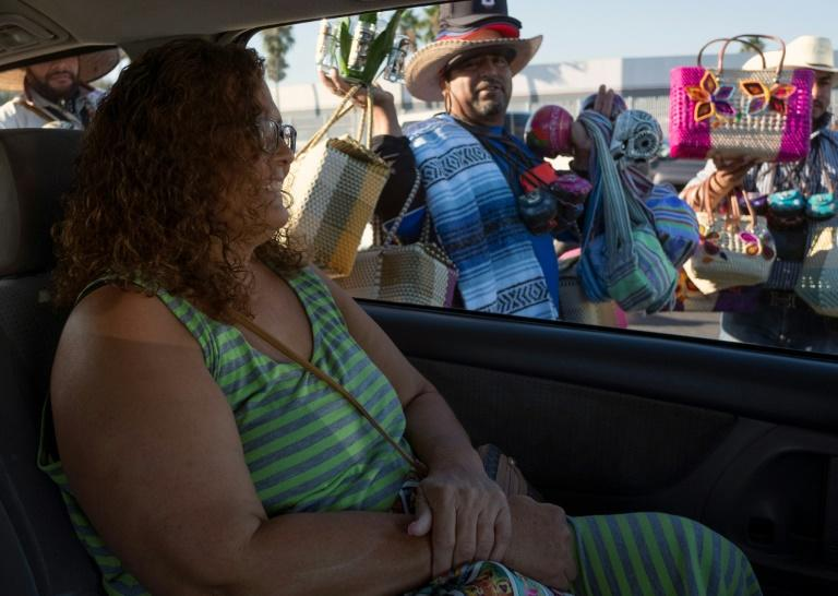 Veronica Merrill smiles at a peddler while heading back to the United States after having a bariatric surgery in Tijuana