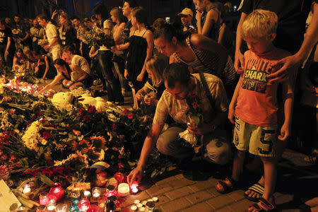 People place candles and flowers at the Dutch embassy to commemorate the victims of Malaysia Airlines MH17, which crashed in eastern Ukraine, in Kiev July 17, 2014. REUTERS/Valentyn Ogirenko