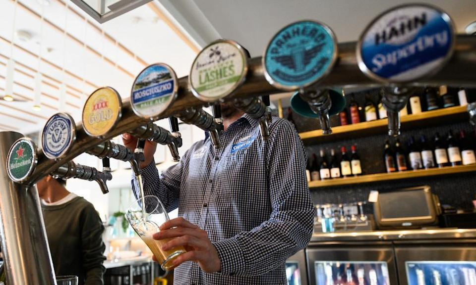A barman pours a beer at a bar in Sydney, Australia