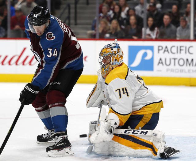Nashville Predators goaltender Juuse Saros, right, makes a glove save of a redirected shot off the stick of Colorado Avalanche center Carl Soderberg during the third period of an NHL hockey game Friday, March 16, 2018, in Denver. The Predators won 4-2. (AP Photo/David Zalubowski)
