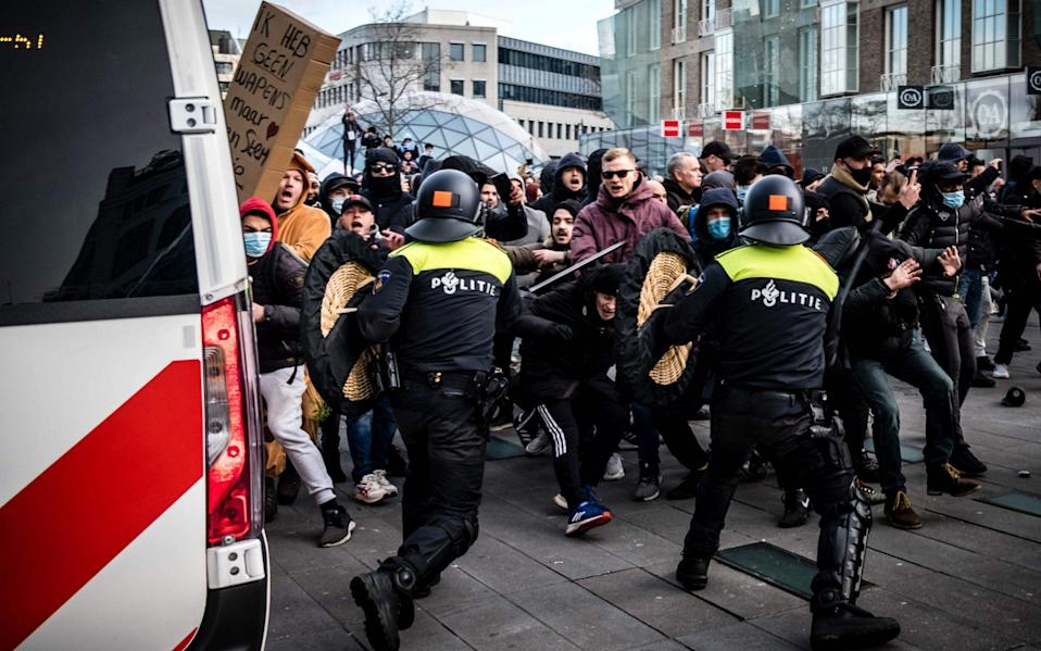 Protesters clash against Dutch anti-riot police officers during a demonstration against coronavirus restrictions in Eindhoven - AFP