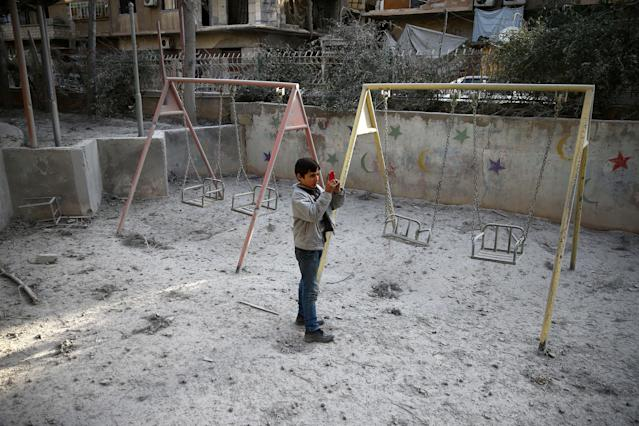 <p>A boy is seen taking pictures after an air raid in the besieged town of Douma in eastern Ghouta in Damascus, Syria, Feb. 6, 2018. (Photo: Bassam Khabieh/Reuters) </p>