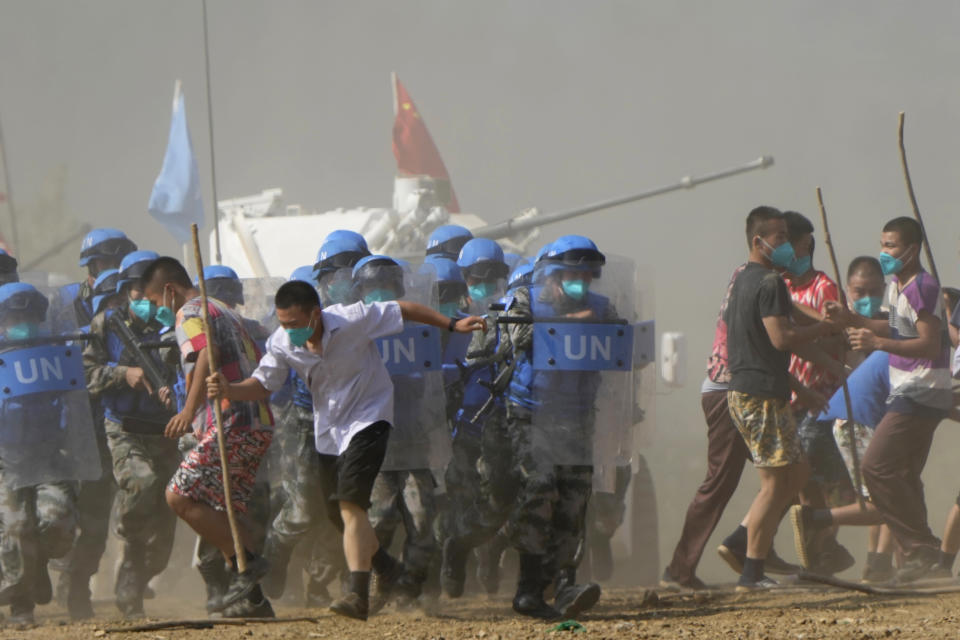 United Nations troop break up fighting in a scenario where participants playing the role of civilians fighting over water resource during the Shared Destiny 2021 drill at the Queshan Peacekeeping Operation training base in Queshan County in central China's Henan province Wednesday, Sept. 15, 2021. Peacekeeping troops from China, Thailand, Mongolia and Pakistan took part in the 10 days long exercise that field reconnaissance, armed escort, response to terrorist attacks, medical evacuation and epidemic control. (AP Photo/Ng Han Guan)