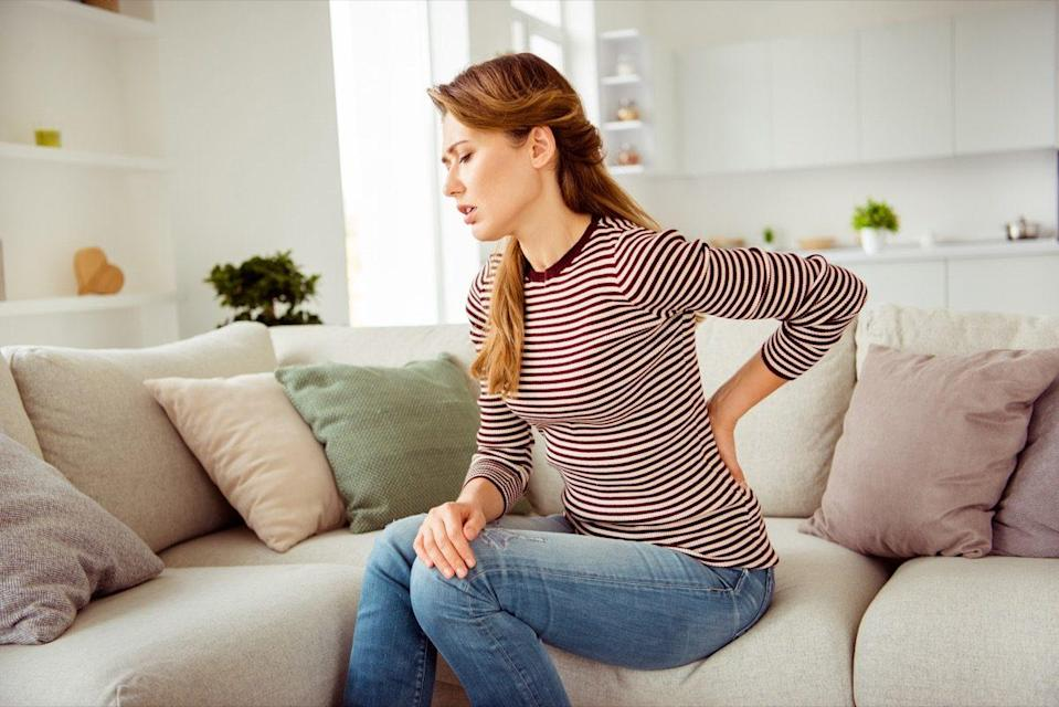 Woman's hands hold back spine suffering pain wear.