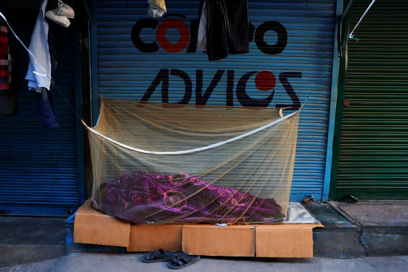 A migrant worker sleeps outside a closed shop at a wholesale market in the old quarters of New Delhi, during a 21-day nationwide lockdown to slow the spreading of the coronavirus disease (COVID-19)