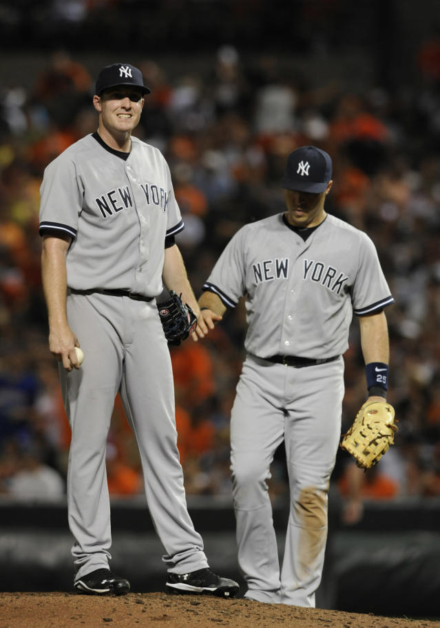 New York Yankees pitcher Chase Whitley, left, pauses on the mound as first baseman Mark Teixeira approaches, after giving up three runs to the Baltimore Orioles in the fourth inning of a baseball game, Sunday, July 13, 2014, in Baltimore.(AP Photo/Gail Burton)