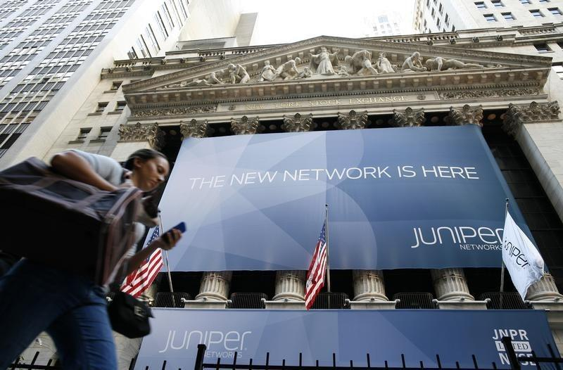 A woman walks past a banner with the logo of Juniper Networks Inc. covering the facade of the New York Stock Exchange