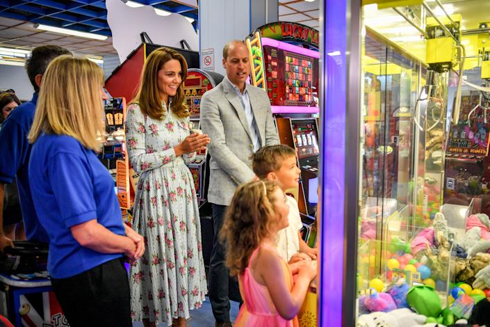 BARRY, WALES - AUGUST 05:  Prince William, Duke of Cambridge and Catherine, Duchess of Cambridge warch children play a grab a teddy game at Island Leisure Amusement Arcade, where Gavin and Stacey was filmed, during their visit to Barry Island, South Wales, to speak to local business owners about the impact of COVID-19 on the tourism sector on August 5, 2020 in Barry, Wales. (Photo by Ben Birchall - WPA Pool/Getty Images)