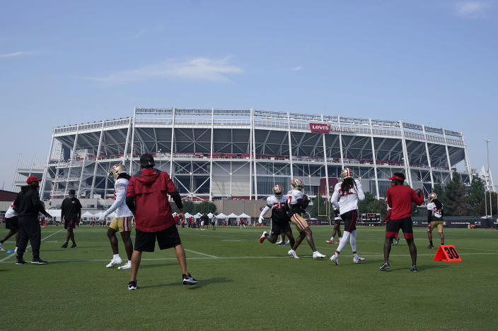 FILE - In this Aug. 22, 2020 file photo, San Francisco 49ers defensive backs run a drill on a field outside of Levi's Stadium during NFL football practice in Santa Clara, Calif. California health officials announced Tuesday, Oct. 20, 2020, that they will allow a limited number of fans to attend professional sporting events in counties with lower rates of transmission of the coronavirus. That includes Santa Clara County, home to the San Francisco 49ers professional football team, but health officials there said they won't allow fans at such events anytime soon. (AP Photo/Jeff Chiu, Pool, File)