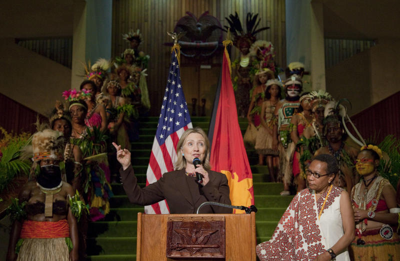 Women in traditional dress stand behind U.S. Secretary of State Hillary Rodham Clinton during an women's empowerment event at Parliament House Wednesday, Nov. 3, 2010 in Port Moresby, Papua New Guinea. (AP Photo/Evan Vucci, Pool)