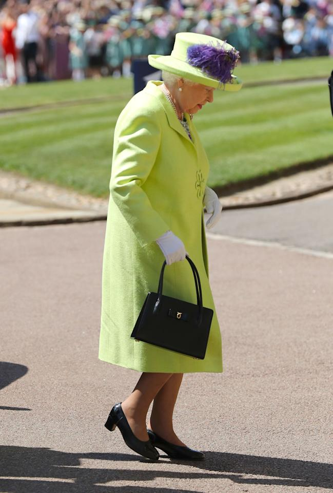 <p>It was bright and bold for the Queen, who arrived shortly before the bride in a lime and purple outfit. Photo: Getty </p>