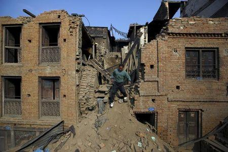 A man walks out from the remaining of a collapsed house in Bhaktapur