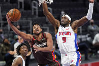 Portland Trail Blazers guard CJ McCollum (3) makes a lap as Detroit Pistons forward Jerami Grant (9) defends during the first half of an NBA basketball game, Wednesday, March 31, 2021, in Detroit. (AP Photo/Carlos Osorio)