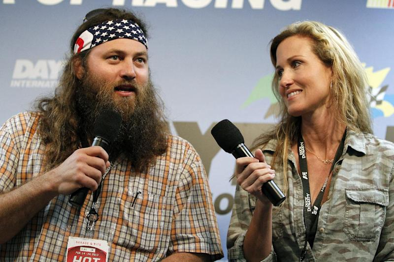 """FILE - This Feb. 24, 2013 file photo shows Willie Robertson, left, and Korie Robertson, of the reality TV show, """"Duck Dynasty"""", before the Daytona 500 NASCAR Sprint Cup Series auto race, at Daytona International Speedway in Daytona Beach, Fla. The nominees for this year's Academy of Country Music Awards will be announced via Twitter and Facebook in a series of videos by TV personalities. Fox Sports broadcaster Erin Andrews, Willie and Korie Robertson from """"Duck Dynasty,"""" Beth Behrs from """"2 Broke Girls"""" and hosts from """"CBS This Morning,"""" ''Entertainment Tonight,"""" ''The Talk"""" and """"The Insider"""" will make the announcements on Jan. 29, 2014. (AP Photo/Terry Renna, File)"""