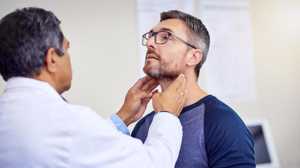 Shot of a confident mature male doctor doing a checkup on a patient while standing inside of a hospital during the day.