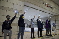 Supporters of the 47 pro-democracy activists charged with conspiracy wave mobile phone lights outside a court in Hong Kong, Friday, March 5, 2021. Four of the 47 pro-democracy activists charged with conspiracy to commit subversion were released on bail Friday, after prosecutors dropped an appeal against the court's decision to grant them bail. (AP Photo/Vincent Yu)