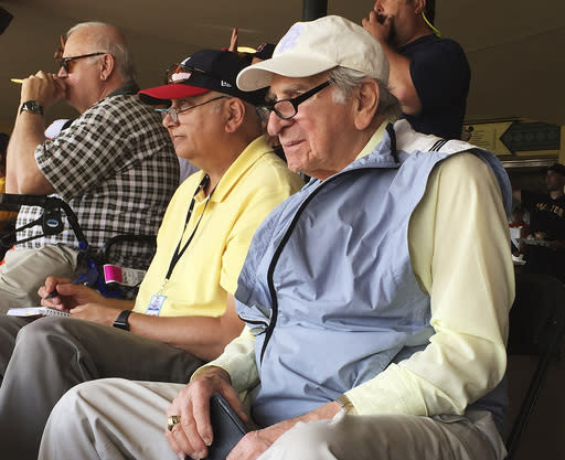 FILE - In this March 5, 2016, file photo, Tommy Giordano, right, special assistant to the general manager of the Atlanta Braves, scouts a spring training baseball game between the Braves and the Pittsburgh Pirates in Kissimmee, Fla. Giordano spent nearly all of his marvelously full life as a baseball man. Hes going out like he lived for more than 93 years _ surrounded by family and friends, accompanied by overwhelming love and stories that will endure long after hes gone. (AP Photo/Paul Newberry, File)
