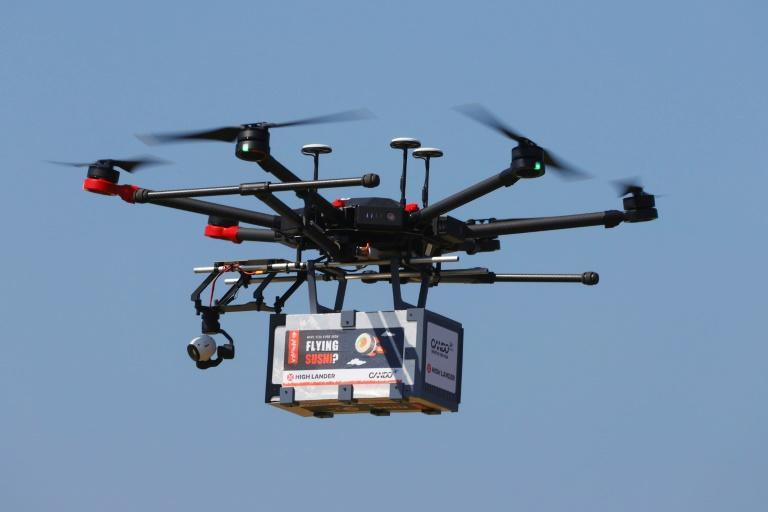 """A drone carrying a box marked """"Flying Sushi"""" is airborne in the Israeli coastal city of Herzliya (AFP/JACK GUEZ)"""