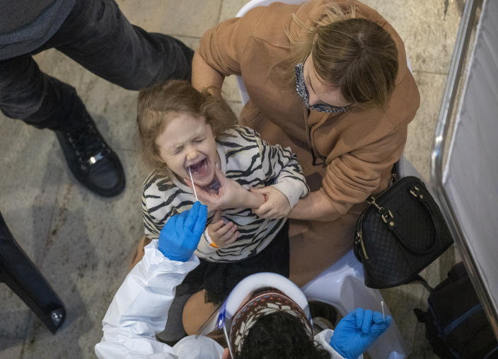 Medical personnel test a passenger for coronavirus as her mother holds her on their arrival in Israel, at Ben Gurion Airport near Tel Aviv, Israel, Sunday, Jan. 24, 2021, during a nationwide lockdown to curb the spread of the COVID-19 virus. (AP Photo/Ariel Schalit)