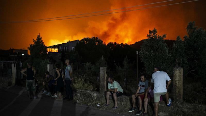 Villagers evacuated and Greek PM cancels holiday as wildfires rage