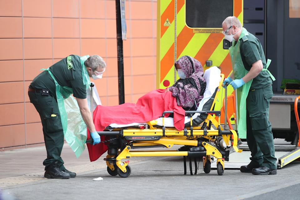 "IMAGE PIXELATED BY PA PICTURE DESK Paramedics transport a patient outside the Royal London Hospital in London. A ""major incident"" was declared by Mayor of London Sadiq Khan last week warning that the spread of coronavirus threatens to ""overwhelm"" the capital's hospitals."