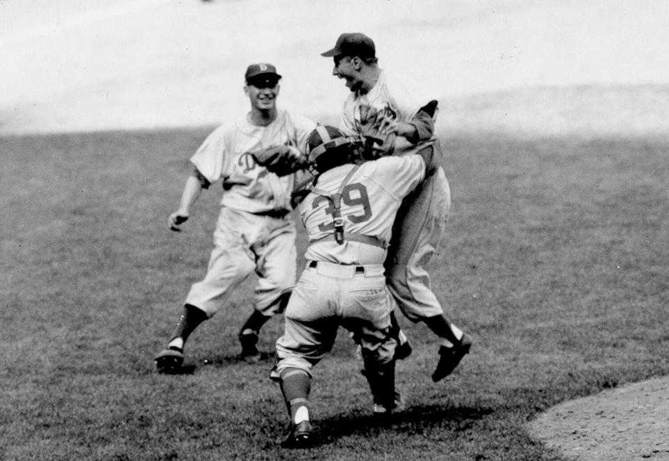 Brooklyn Dodgers pitcher Johnny Podres is lifted by catcher Roy Campanella after the final out of Game 7.