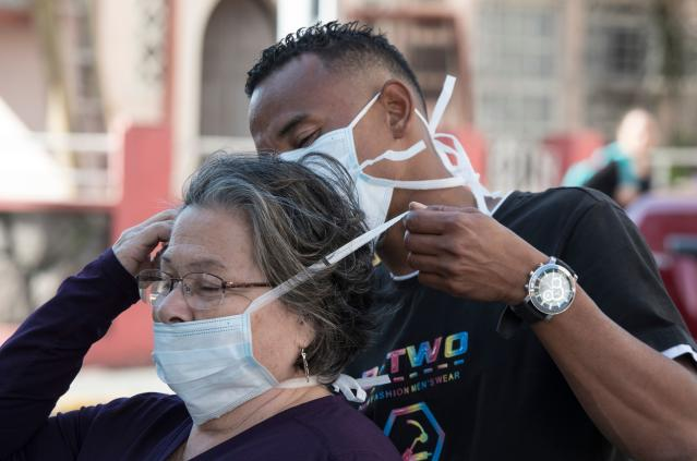 A man puts a face mask on a woman as a preventive measure against COVID-19, in San Jose, Costa Rica. (AP)