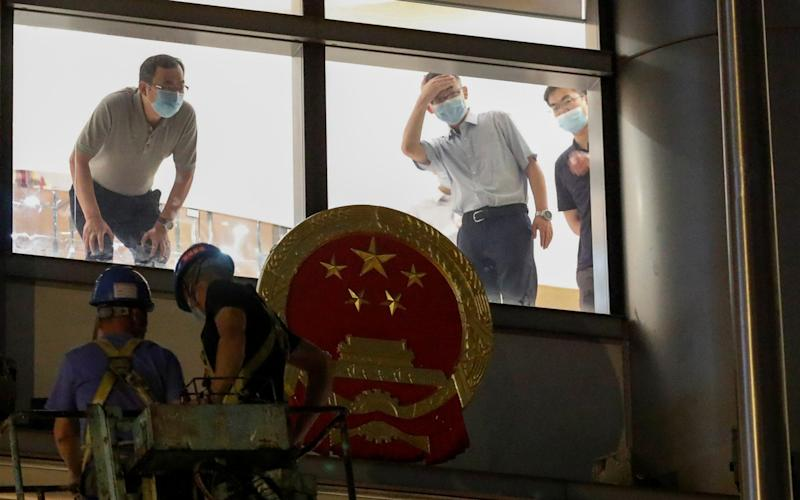 Workers place a national emblem outside the Metropark Hotel Causeway Bay Hong Kong - Reuters