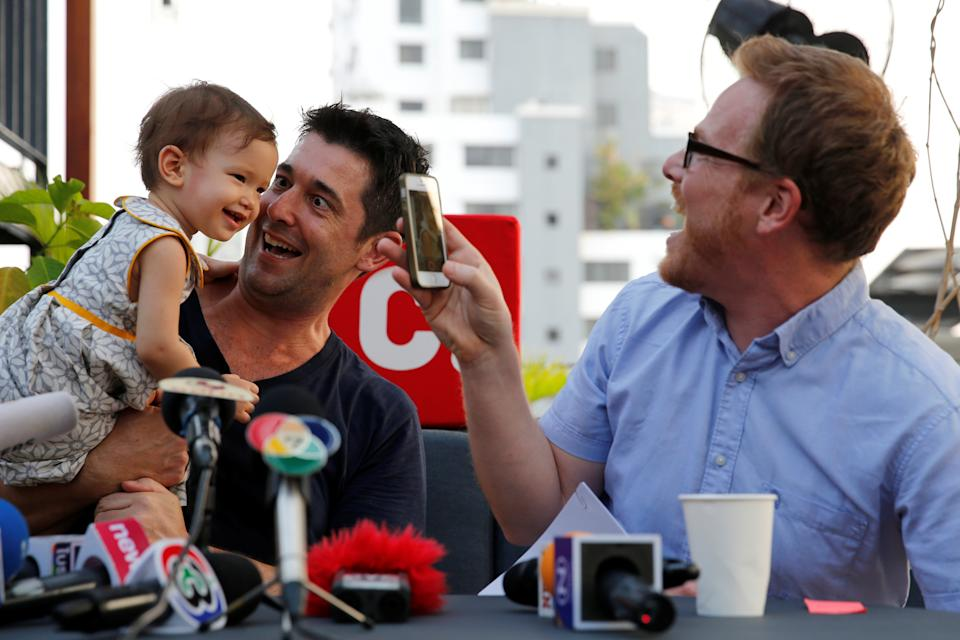 U.S. citizen Gordon Lake (R), his Spanish husband Manuel Santos and their baby Carmen attend a news conference after they won an appeal for parental rights over a baby born through a Thai mother before the Thai ban on commercial surrogacy came into effect last year, Bangkok, Thailand April 29, 2016.  REUTERS/Jorge Silva