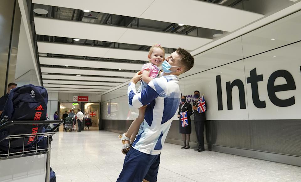 Olympic gymnast Max Whitlock hugs his daughter Willow as he arrives back at London Heathrow Airport from the Tokyo 2020 Olympic Games. Picture date: Tuesday August 3, 2021.