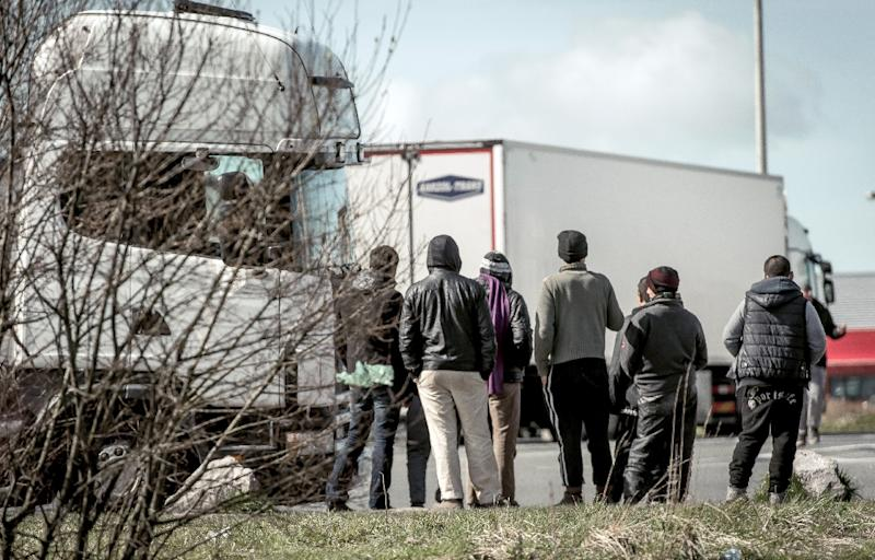 Migrants stand looking at lorries stationed in a parking lot in Marck, just north of the sea port of Calais on the English Channel on March 30, 2016