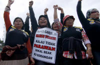 """In this Friday, Dec. 21, 2012 photo, Indonesian women shout slogans during a protest demanding District Chief Aceng Fikri to step down, in Garut, West Java, Indonesia. The Supreme Court late last month recommended that the president dismiss Fikri for violating the marriage law, following a public outrage after he divorced his second teenage wife by text message just four days after their wedding. The response has been seen as a small step forward for women's rights in the secular country where most people practice a moderate form of Islam. The writings on the poster reads """"Garut District Chief must step down or there will be no more virgins."""" (AP Photo/Kusumadireza)"""